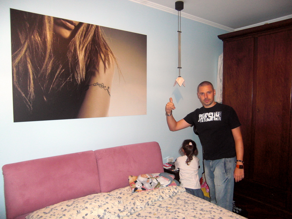 Paolo in his bedroom, with a giant picture of Verusca